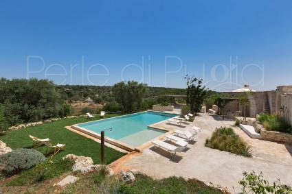 Una panoramica della piscina con solarium, doccia esterna e vista sull`uliveto
