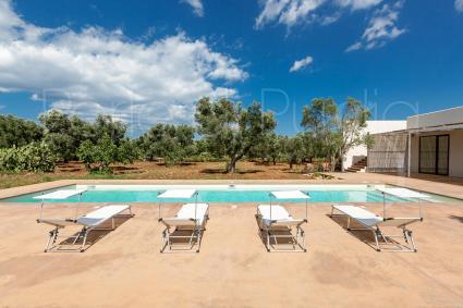 Rilassarsi a bordo piscina sui lettini del solarium