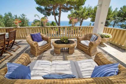 The patio overlooking the sea is shaded and furnished with sofas
