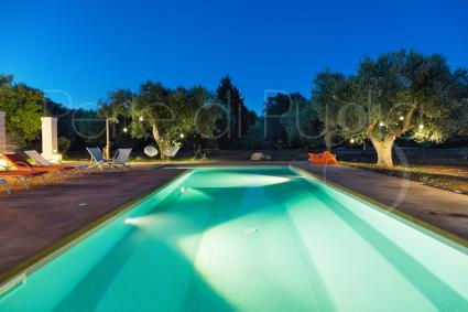 In the evening, the illuminated swimming pool envelops the villa with charm and magic