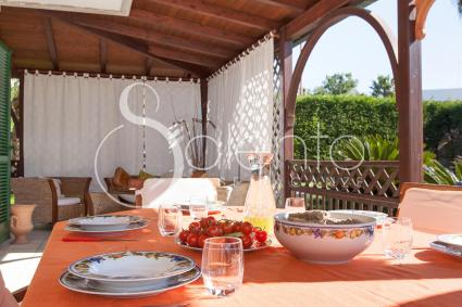 The shaded veranda is furnished with a dining room and relaxing sofas