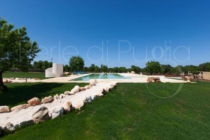 Un vialetto di pietre unisce la piscina ai trulli