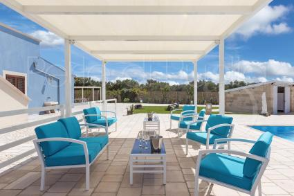 The gazebo provides shade to the sofas and armchairs, for relaxing by the pool