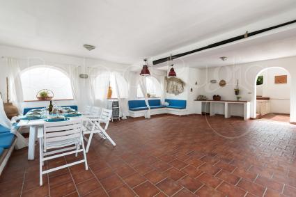 Il grande patio coperto, con divani e area pranzo, aperto sul giardino
