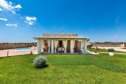 The lawn frames the rustic-style villa and typical architecture of Salento