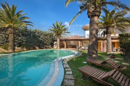 La bella piscina con zona solarium su prato inglese