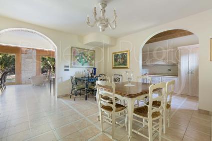La sala da pranzo con cucinino oltre l`arco