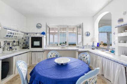 The kitchen is white, blue, with view on the sea