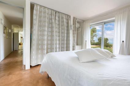 Double bedroom with glass walls and view on the swimming pool and garden