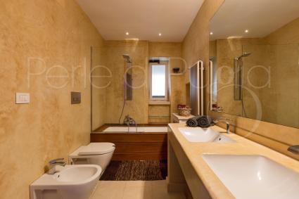 Il bagno con vasca, doccia e doppio lavabo è spazioso, moderno ed elegante