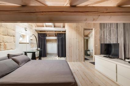 Volte in legno, pietre a vista, stile minimal per la terza camera