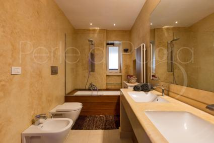 The bathroom with bath, shower and double sink is spacious, modern and elegant