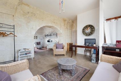 Il salone con divani, scrivania e porta d`ingresso principale