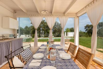 Ampia veranda con vetrate e cucina esterna