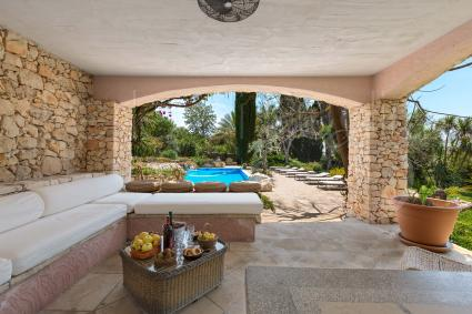 Bellissimo salotto nei pressi della piscina, con divano in pietra e grandi cuscini su misura